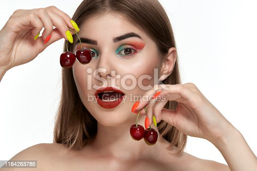 istock Closeup portrait of a beautiful young woman with bright color make-up holding strawberry near the face. 1164263785