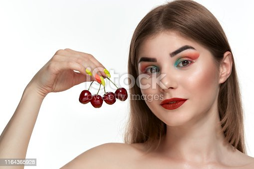 istock Closeup portrait of a beautiful young woman with bright color make-up holding strawberry near the face. 1164365928