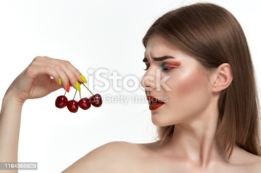 istock Closeup portrait of a beautiful young woman with bright color make-up holding strawberry near the face. 1164365929
