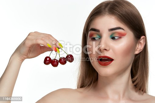 istock Closeup portrait of a beautiful young woman with bright color make-up holding strawberry near the face. 1164365930