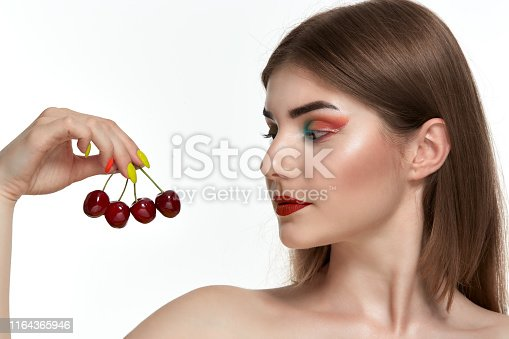 istock Closeup portrait of a beautiful young woman with bright color make-up holding strawberry near the face. 1164365946