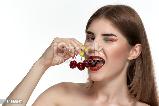 istock Closeup portrait of a beautiful young woman with bright color make-up holding strawberry near the face. 1164365947