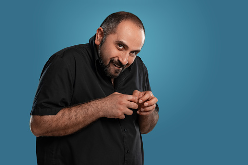 Close-up portrait of a brunet middle-aged man with beard, dressed in a black t-shirt and posing against a blue background