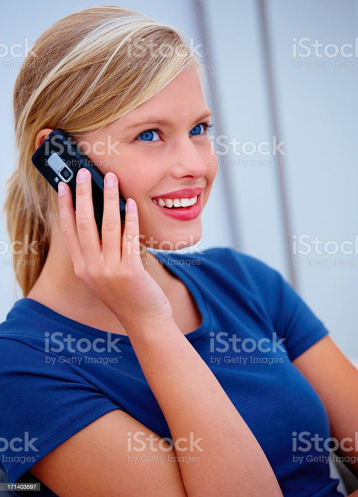 Closeup portrait of a cute smiling young woman using a cellphone royalty-free stock photo