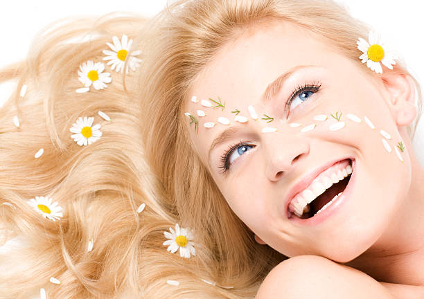 Close-up portrait of a fresh and beautiful woman with camomile stock photo
