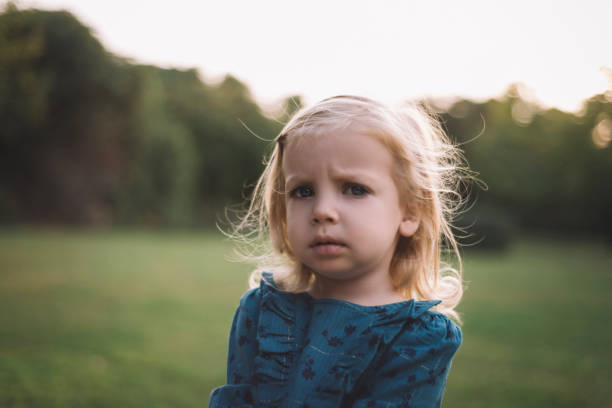 Close-up portrait of a frustrated little girl looking at camera with sad facial expression stock photo