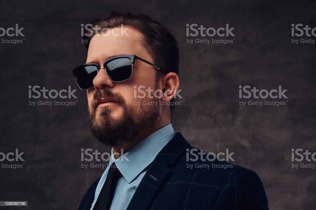 34b5ac1edc97 Close-up portrait of a handsome fashionable middle-aged man with beard and  hairstyle dressed in an elegant formal suit and sunglasses.