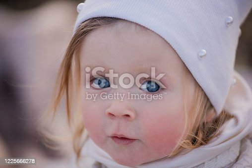 istock A close-up portrait of a little girl with a blush on her cheeks, blue eyes, a blonde and a white hat. 1225666278