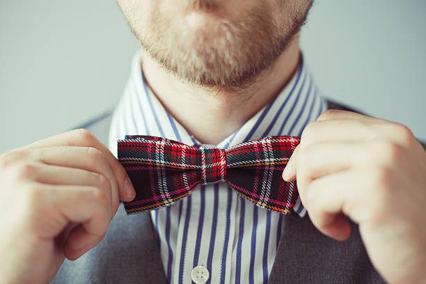 Close-up portrait of a man correcting bowtie Close-up photo of a man with bard correcting his bow-tie bow tie stock pictures, royalty-free photos & images