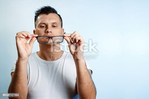 951331990 istock photo A close-up portrait of a man who straightens his glasses with his hands. On a light background. 953810164