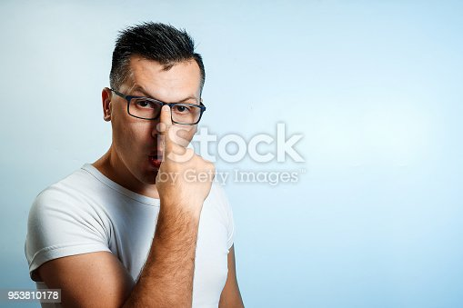 951331990 istock photo A close-up portrait of a man who straightens his glasses with his hands. On a light background. 953810178