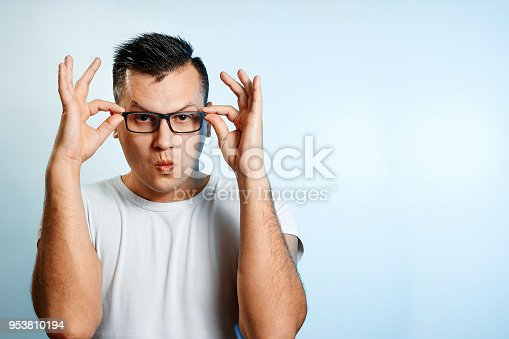 951331990 istock photo A close-up portrait of a man who straightens his glasses with his hands. On a light background. 953810194