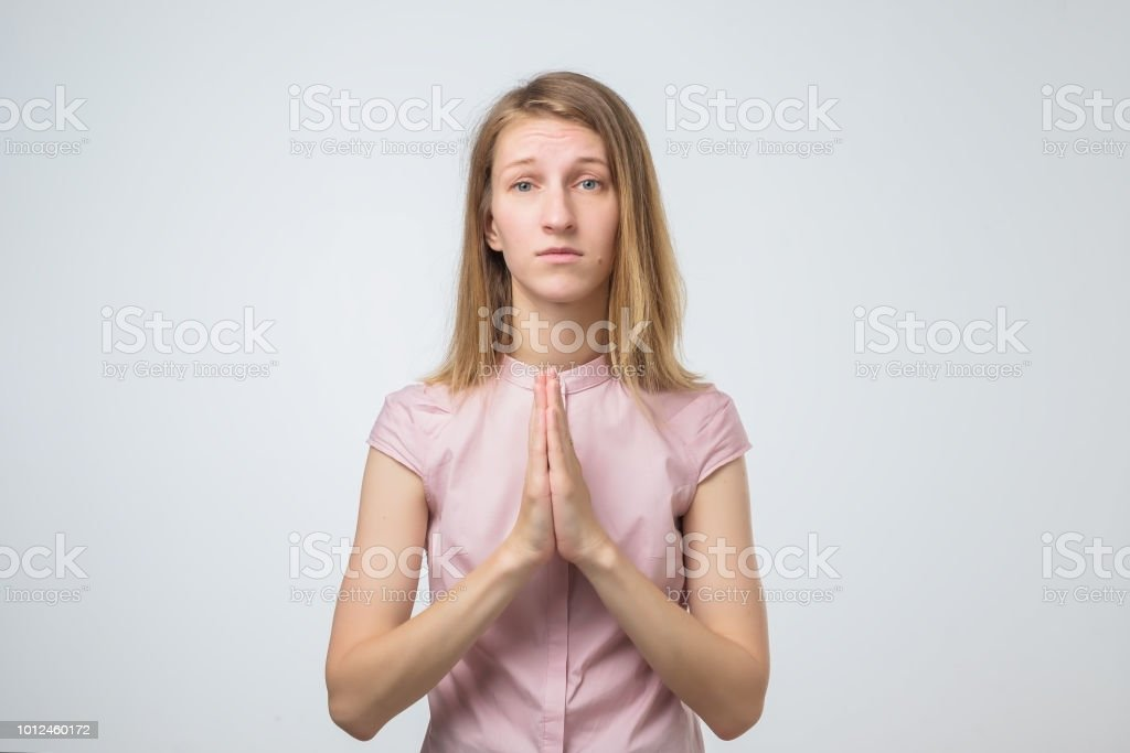 Closeup portrait of a sad young woman praying, hoping, begging for the best isolated on white background stock photo