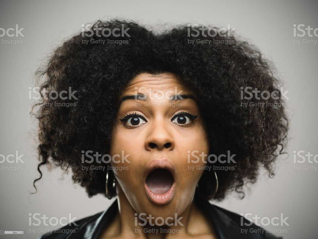 Close-up portrait of a shocked real young afro american woman stock photo