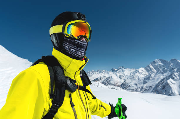 Close-up portrait of a skier in a mask and helmet with a closed face against a background of snow-capped mountains and blue sky stock photo