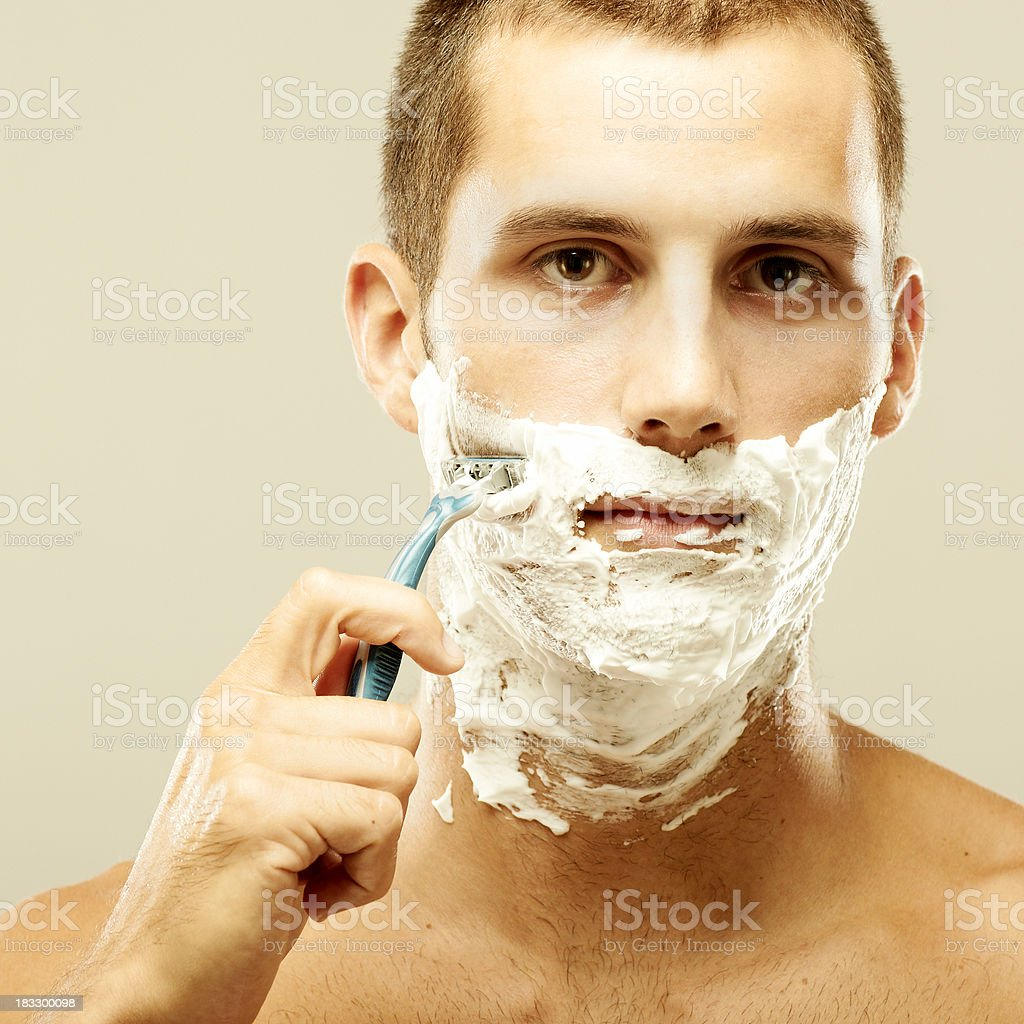 Closeup portrait of a smart young man shaving royalty-free stock photo