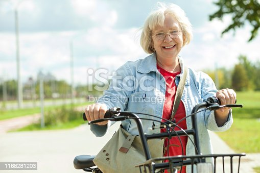 Closeup portrait of a smiling 70 year old woman on bicycle with glasses and in a blue denim jacket