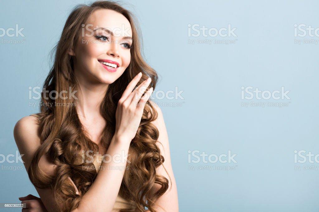 微笑美麗的女人,用長長的卷髮的特寫肖像。 免版稅 stock photo