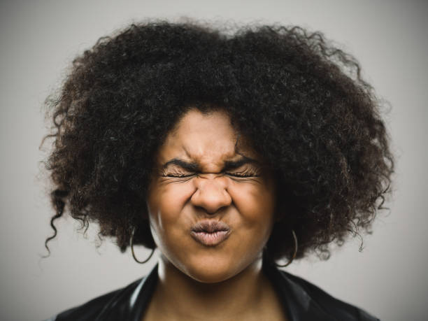 Close-up portrait of a stressed real young afro american woman Close-up portrait of stressed real young afro american woman clenching eyes. Shocked female against gray background. Horizontal making a face stock pictures, royalty-free photos & images