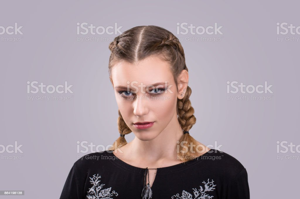 closeup portrait of a teenage girl with braided pigtails standing in front of a and gray background royalty-free stock photo