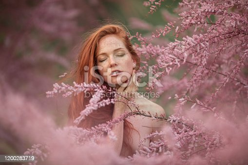 1054970060 istock photo Close-up portrait of a woman in the pink branches of a flowering peach tree 1200283719