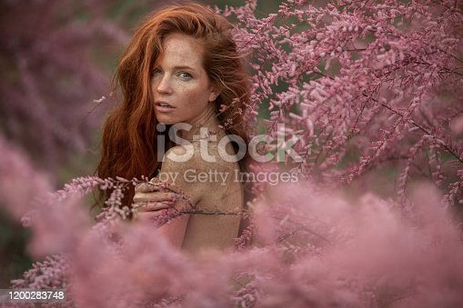 1054970060 istock photo Close-up portrait of a woman in the pink branches of a flowering peach tree 1200283748