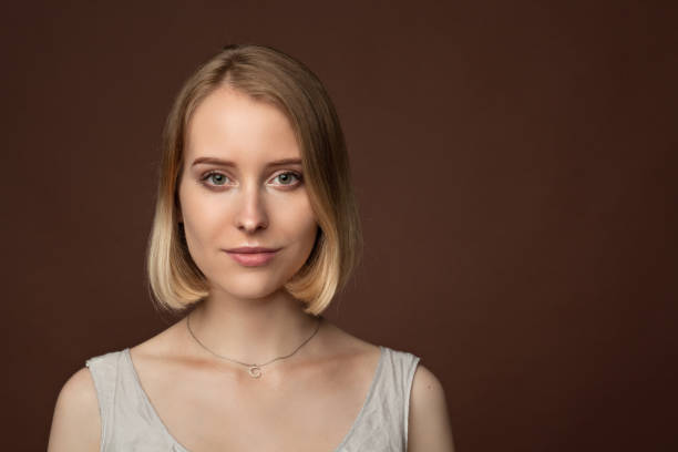 close-up portrait of a young attractive woman 20 years in a dress in the studio on a brown background stock photo
