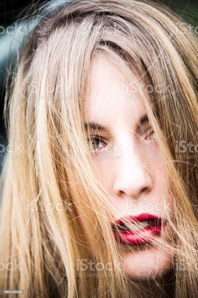 Close-up portrait of a young blonde woman, her eyes covering by her hair. royalty-free stock photo
