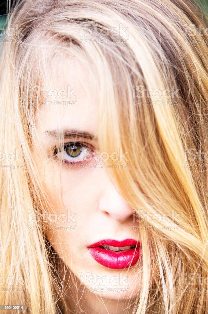 젊은 금발의 여자, 그녀의 머리에 의해 덮고 그녀의 눈의 클로즈업 초상화. - 로열티 프리 곁눈질 스톡 사진