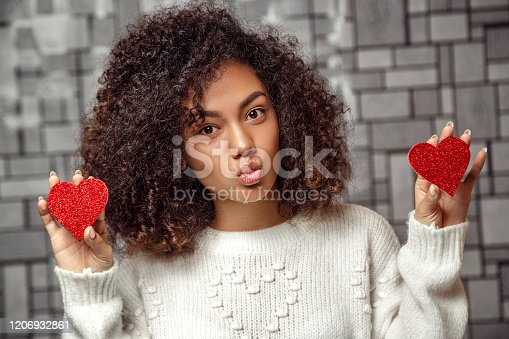 istock close-up Portrait of a young curly-haired African-American girl in a white sweater holding two paper hearts and blowing a kiss .  low depth of focus 1206932861
