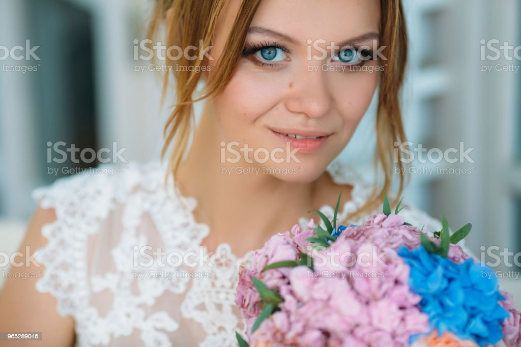 Close-up portrait of a young girl. Beautiful blue eyes look directly into the camera. The bride with an unforgettable look enjoys the wedding day zbiór zdjęć royalty-free