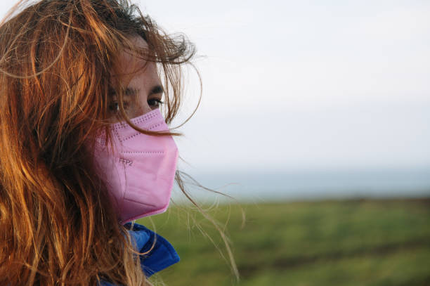 Close-up portrait of a young woman wearing a pink FFP2 mask stock photo