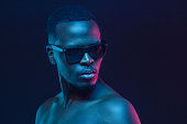 istock Close-up portrait of african man standing in sunglasses and with naked shoulders in neon light 1150254188