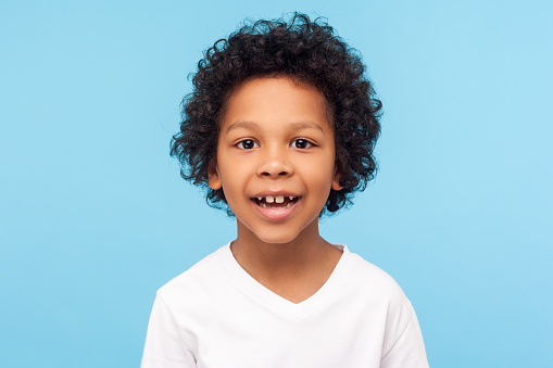 Closeup portrait of amazing cheerful little boy with curly hairdo in white T-shirt looking at camera with happy carefree smile