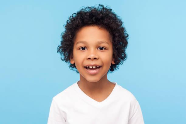 närbild porträtt av fantastiska glad liten pojke med lockig frisyr i vit t-shirt tittar på kameran med glad sorglös leende - 6 7 år bildbanksfoton och bilder
