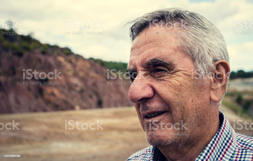 Close-up portrait of an elderly smiling man with white hair and plaid shirt stock photo
