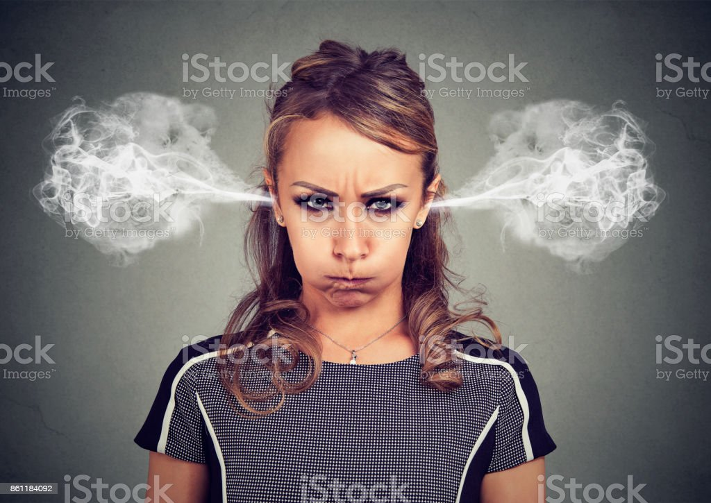 Closeup portrait of angry young woman, blowing steam coming out of ears isolated gray background. Negative human emotions facial expression feelings stock photo