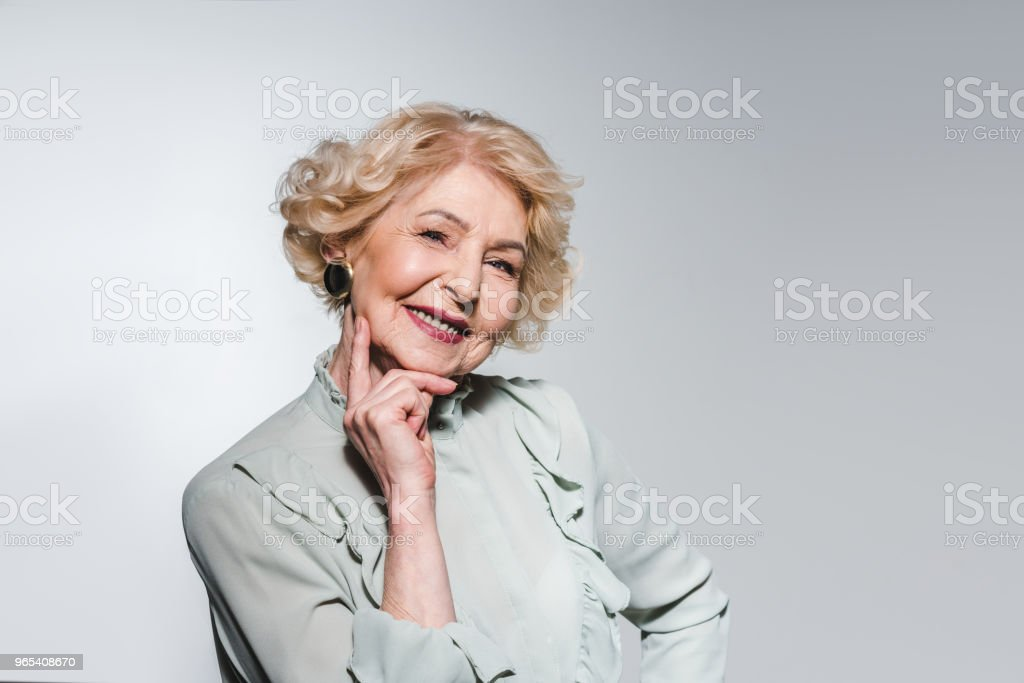 close-up portrait of attractive senior woman isolated on grey zbiór zdjęć royalty-free