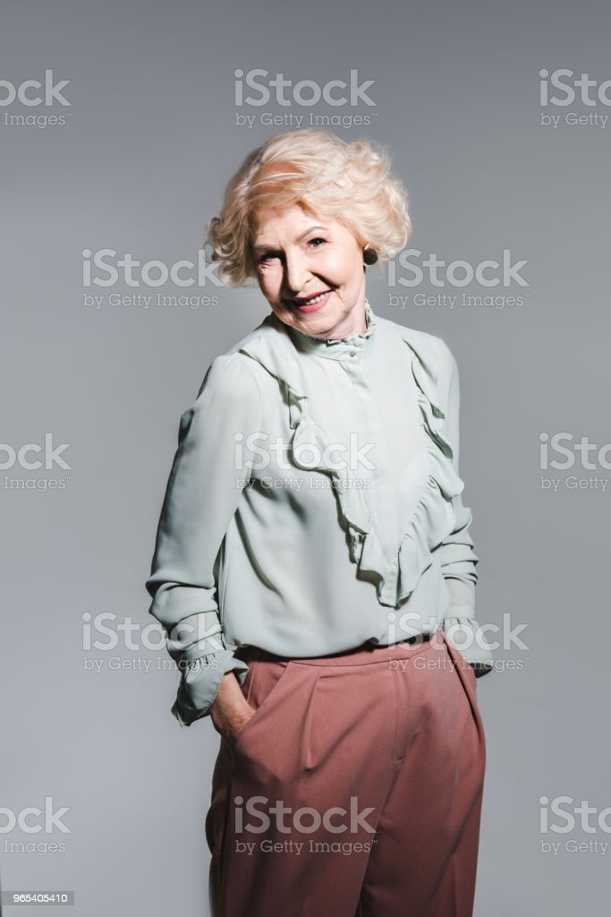 close-up portrait of beautiful senior woman isolated on grey royalty-free stock photo