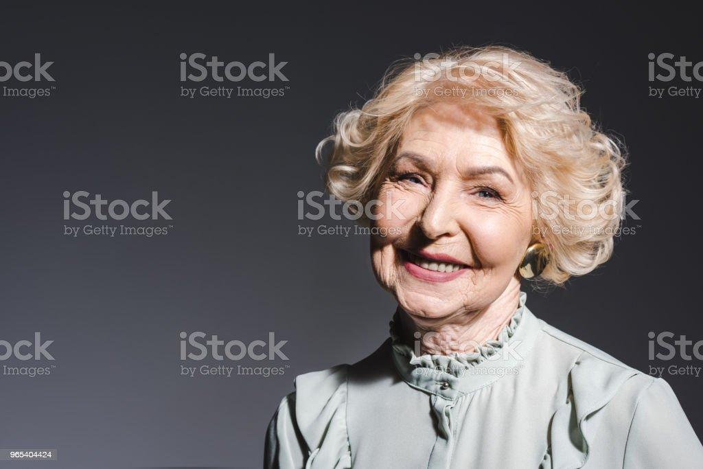 close-up portrait of beautiful senior woman looking at camera on dark grey zbiór zdjęć royalty-free
