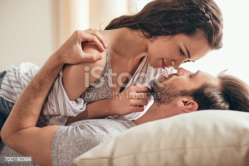 istock Close-up portrait of beautiful sensual young couple hugging while lying on bed 700190366