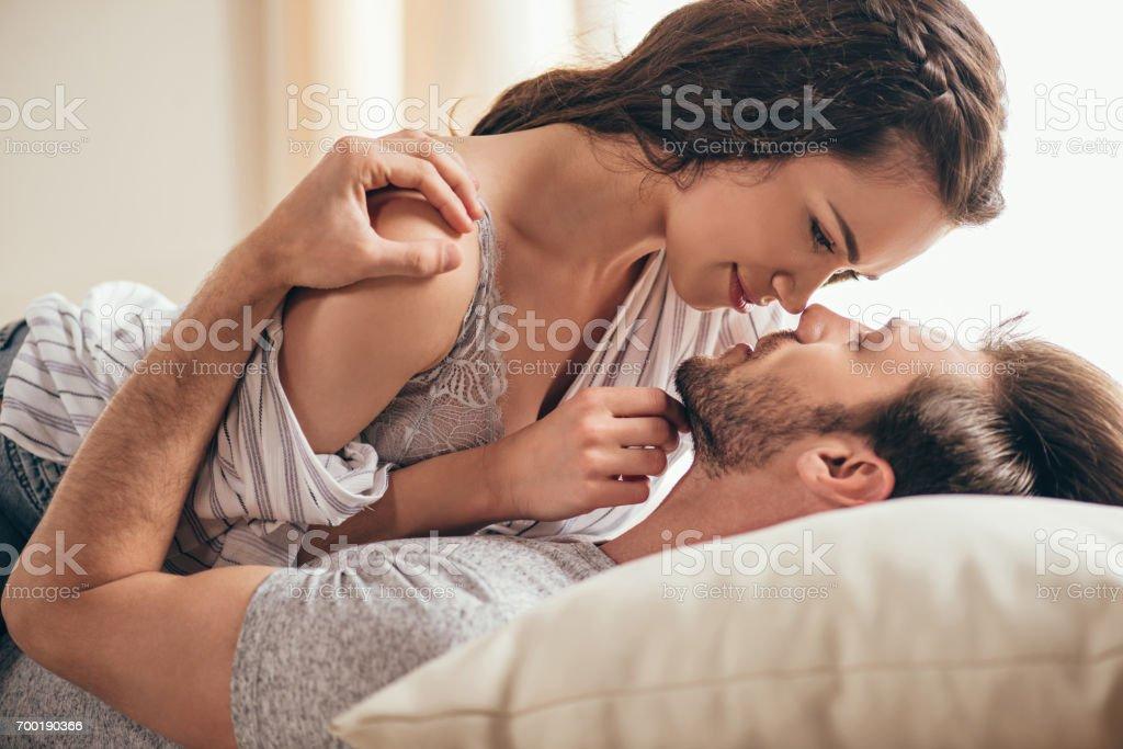 Primer plano retrato de hermosa sensual joven pareja abrazarse mientras se está acostado en la cama - foto de stock