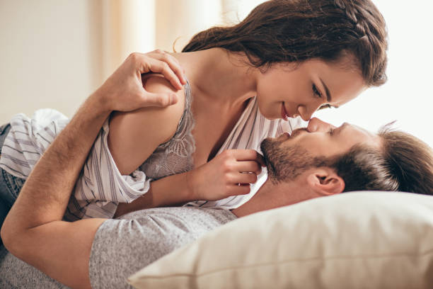 Close-up portrait of beautiful sensual young couple hugging while lying on bed stock photo