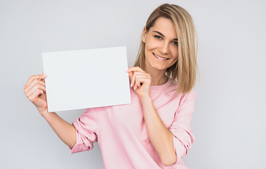 istock Closeup portrait of beautiful smiling blonde female wearing pink sweater, posing with white blank paper with copy space for your advertisement information and looking at camera, against white wall. 951345114