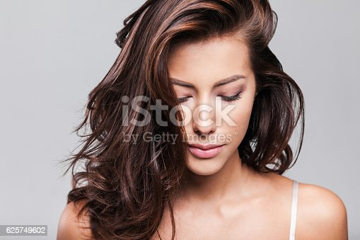 istock Close-up portrait of beautiful woman looking down 625749602
