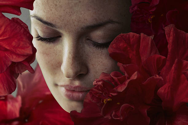 close-up portrait of beautiful women in red flowers close-up portrait of beautiful women in red flowers dark spots face stock pictures, royalty-free photos & images