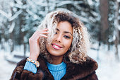 istock Close-up portrait of beautiful young afro american woman in snow winter forest 1094583496