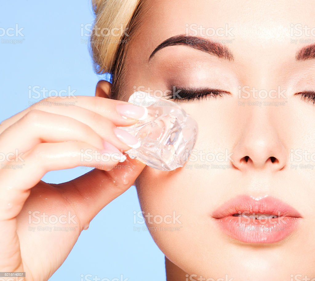 Closeup portrait of beautiful young woman applies ice to face stock photo