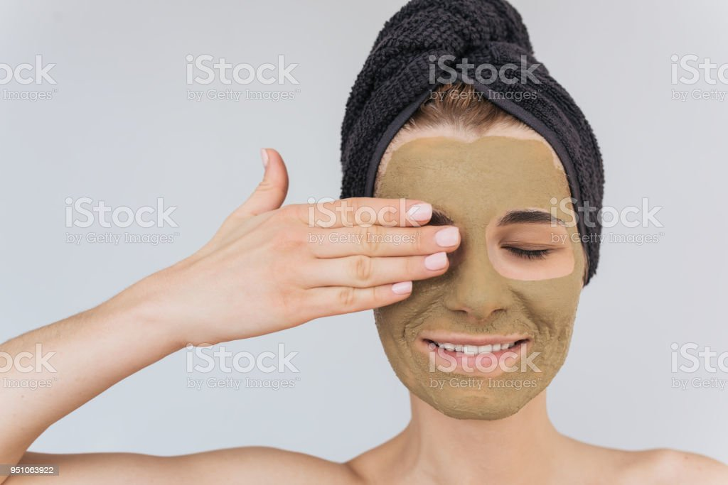 a820bc7383f Closeup portrait of beautiful young woman doing beauty treatment on her face  clean skin with clay