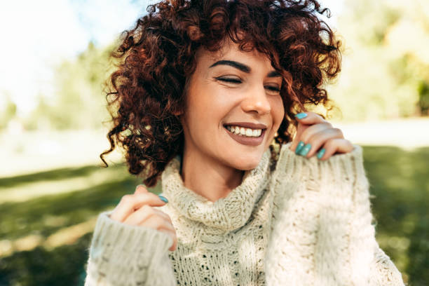 Close-up portrait of beautiful young woman smiling broadly with toothy smile, posing against nature background with curly hair, have positive expression, wearing knitted sweater. People, lifestyle stock photo